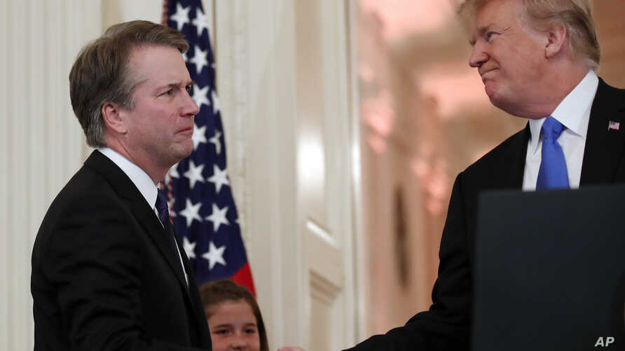 President Donald Trump shakes hands with Judge Brett Kavanaugh his Supreme Court nominee, in the East Room of the White House, July 9, 2018, in Washington.