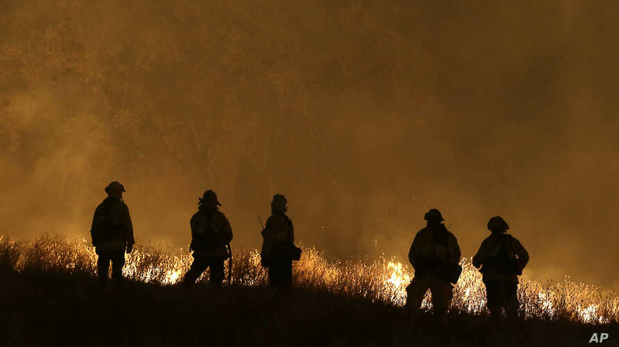 Firefighters stand guard as flames from the Butte Fire approach a containment line in San Andreas, California, Sept. 12, 2015.