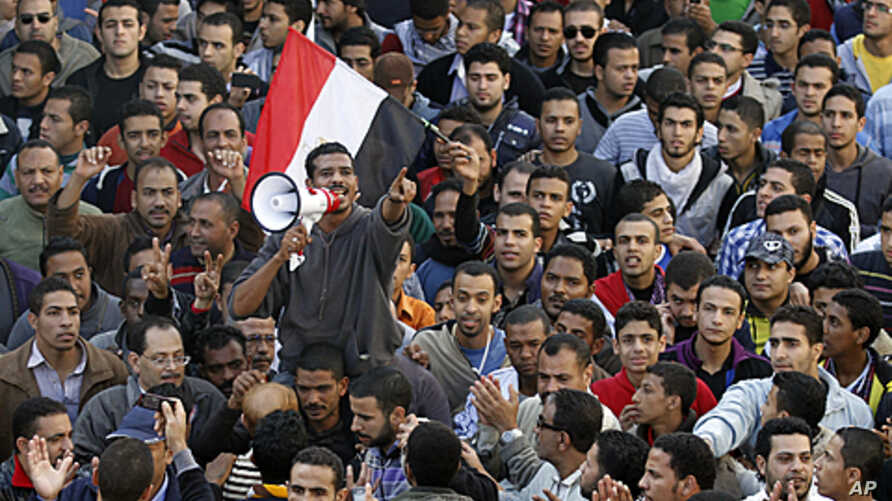 A demonstrator uses a portable loudspeaker as he shouts slogans against the military council during a mass protest in Alexandria, in support of mass protests in Tahrir square in Cairo, November 25, 2011.