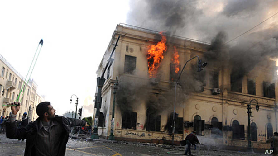 An Egyptian protester uses a slingshot against soldiers, unseen, as a building burns during clashes near Tahrir Square, in Cairo, Egypt, December 17, 2011.
