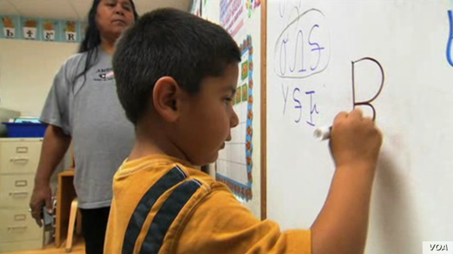 Oklahoma Cherokee language immersion school student writing in the Cherokee syllabary.