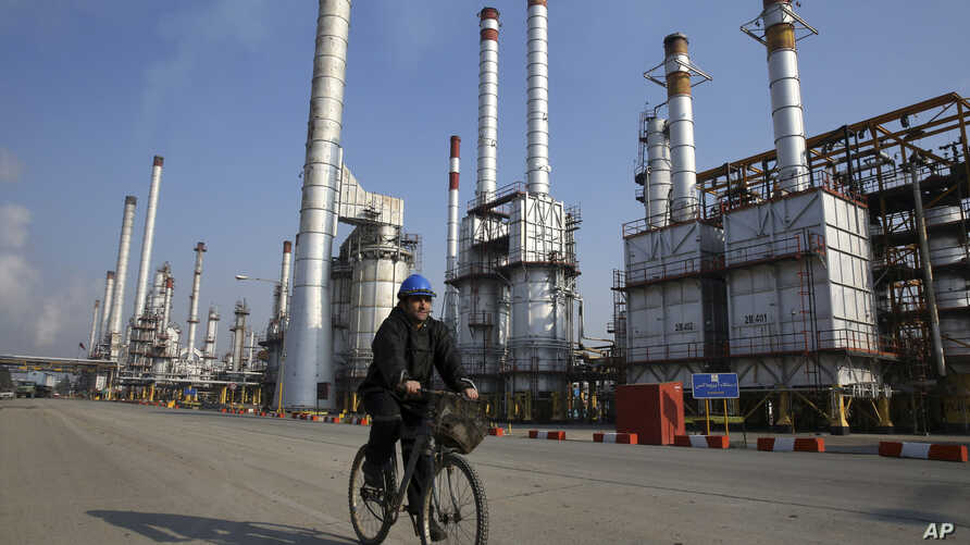 FILE - Iranian oil worker rides his bicycle at the Tehran's oil refinery south of the capital Tehran, Iran.