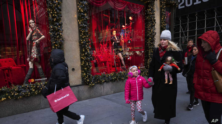 FILE - People walk by holiday windows at Saks Fifth Avenue in New York,Dec. 5, 2018.