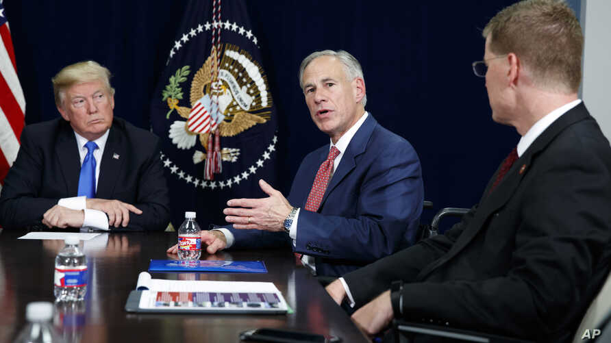 President Donald Trump listens as Texas Gov. Greg Abbott speaks during a briefing on hurricane recovery efforts, Oct. 25, 2017, in Dallas.