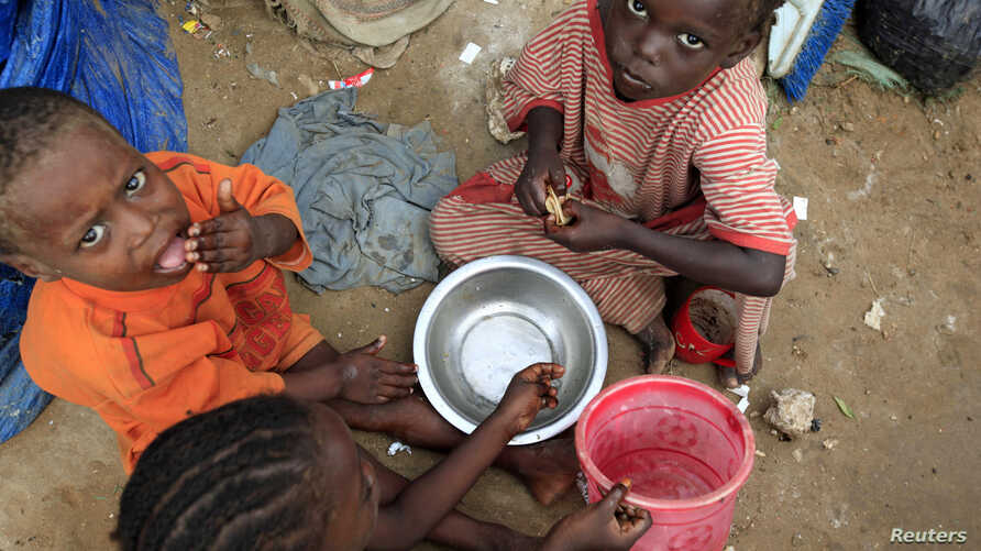 Internally displaced Somali children eat breakfast at Sayyidka camp in the Howlwadag district, south of Somalia's capital Mogadishu, May 3, 2013.