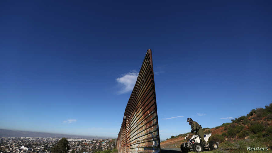 FILE - A member of the U.S. border patrol inspects the area where the border fence separating Mexico and the United States is interrupted, on the outskirts of Tijuana, Mexico, Feb. 21, 2017.