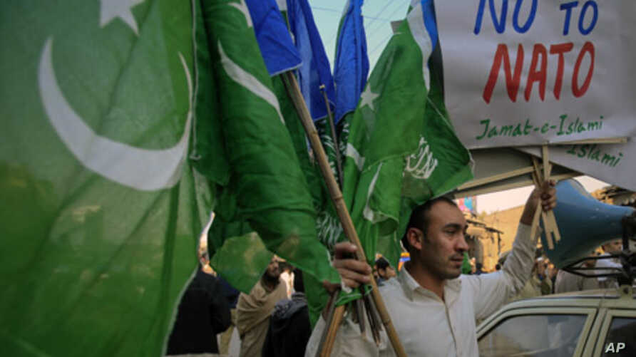 A supporter of Jamaat-e-Islami, a religious and political party, holds collected party flags and placards after an anti-American demonstration in Peshawar, December 2, 2011.