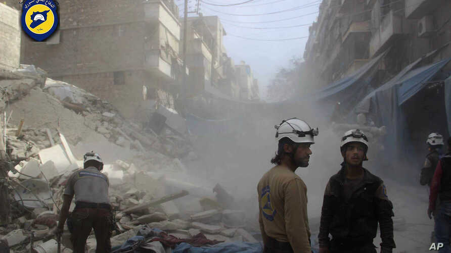 In this picture provided by the Syrian Civil Defense group known as the White Helmets, Syrian Civil Defense workers search through the rubble in rebel-held eastern Aleppo, Syria, Oct. 12, 2016.