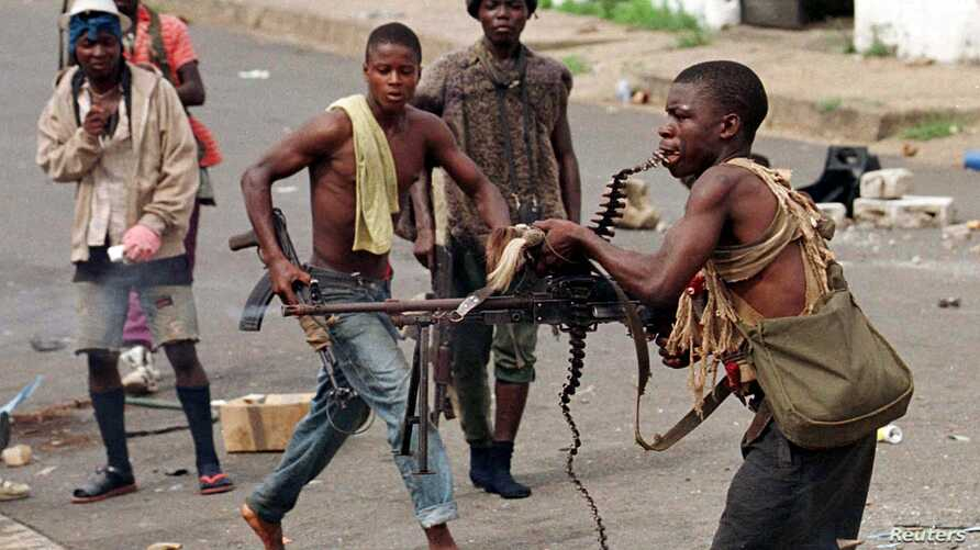 FILE - May 8, 1996 photo shows a street fighter with Charles Taylor's NPFL firing his machine gun while holding the string of bullets in his teeth during a heavy exchange.