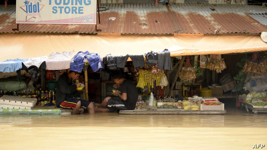 Vendors eat their lunch as they wait for customers at a flooded market in Candaba, Pampanga, north of Manila, Dec. 18, 2015.