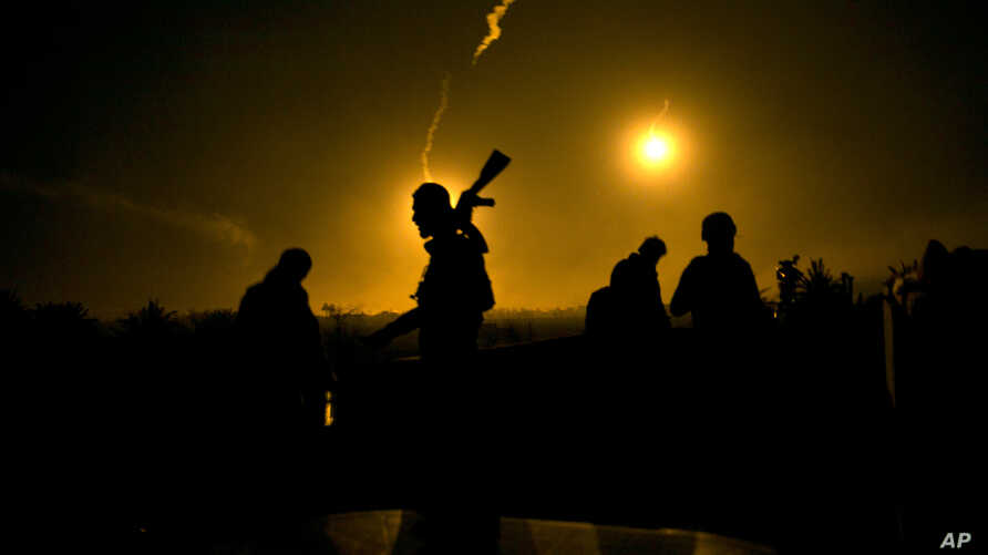 A U.S.-backed Syrian Democratic Forces (SDF) fighter watches illumination rounds light up Baghouz, Syria, March 12, 2019, as the last pocket of Islamic State militants is attacked.