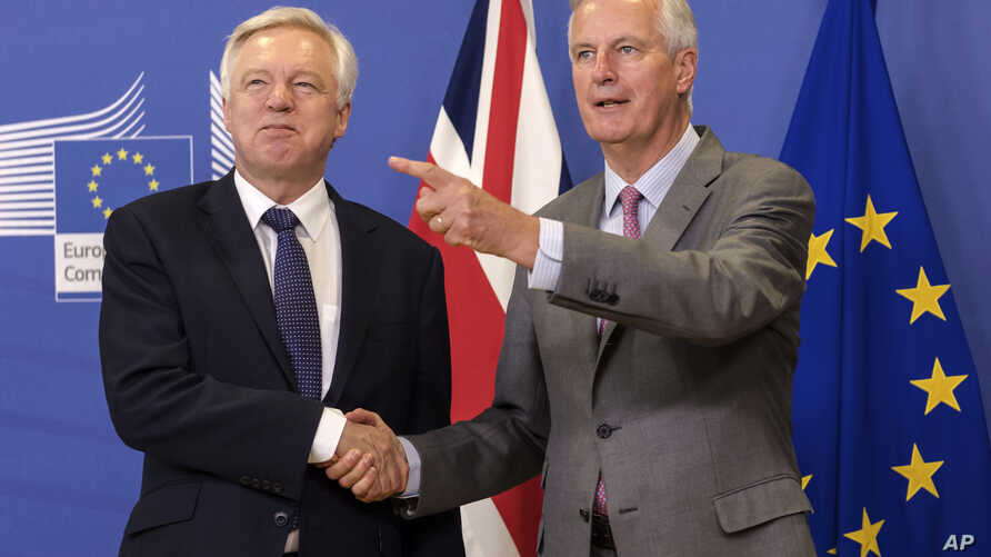 EU chief Brexit negotiator Michel Barnier, right, welcomes British Secretary of State David Davis for a meeting at the EU headquarters in Brussels, July 17, 2017.