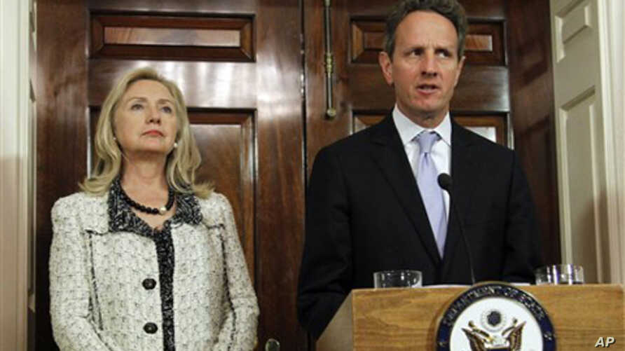 Secretary of State Hillary Rodham Clinton, left, listens to Treasury Secretary Tim Geithner, speak about new sanctions the U.S. is taking to increase pressure on Iran, at the State Department in Washington, Monday, Nov. 21, 2011.