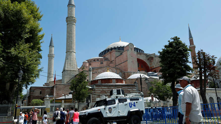Tourists enter the Byzantine-era monument of Hagia Sophia as they pass by an armoured police vehicle in the Old City of Istanbul, Turkey, July 13, 2016.