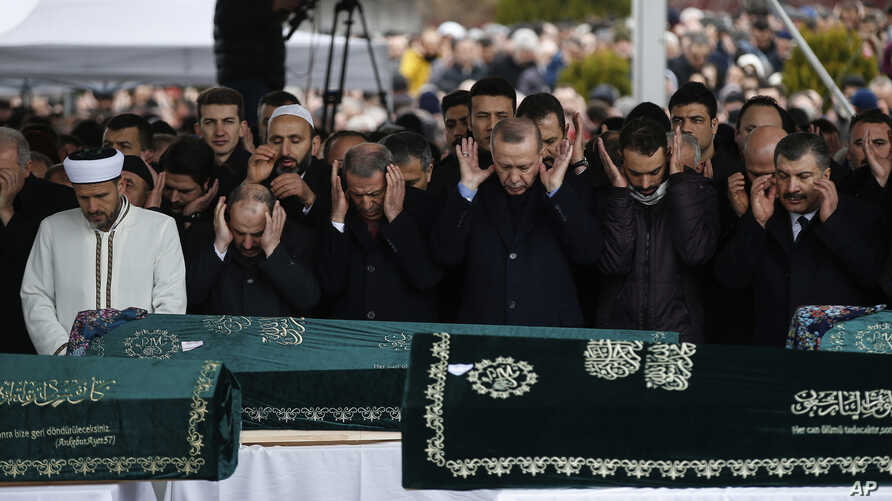 Turkey's President Recep Tayyip Erdogan, center, joins hundreds of mourners who attend the funeral prayers for nine members of Alemdar family killed in a collapsed apartment building, in Istanbul, Saturday, Feb. 9, 2019.