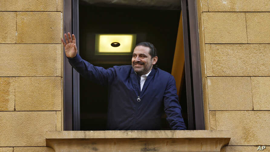 Lebanese Prime Minister Saad Hariri waves to his supporters from a window of his residence, in Beirut, Lebanon, Nov. 22, 2017.