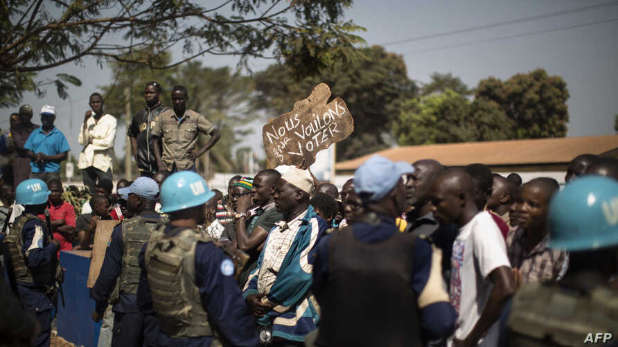 "Residents of the PK5 district hold a banner reading ""We want to vote"" as they demonstrate in front of the MINUSCA, the United Nations mission in Central African Republic's headquarters, calling for more security measures outside of the polling statio"