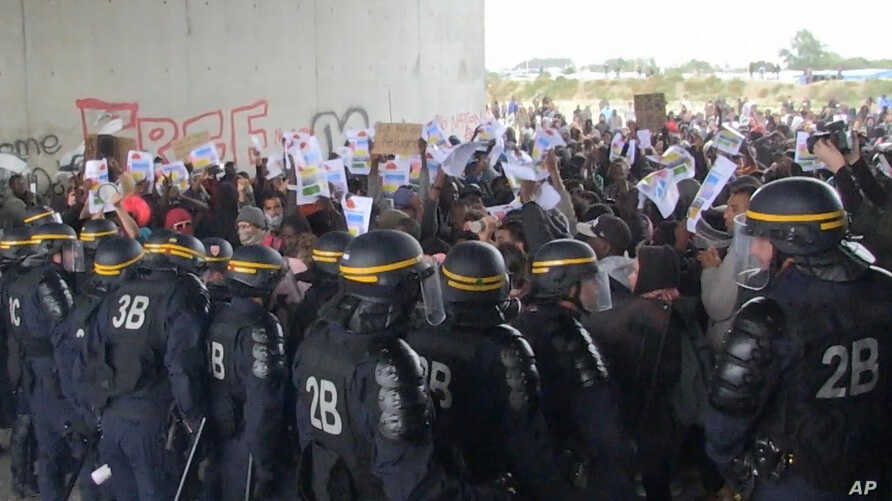 In this grab taken from video, police control protesters, during a demonstration near the migrant camp,  in Calais, France, Oct. 1, 2016.