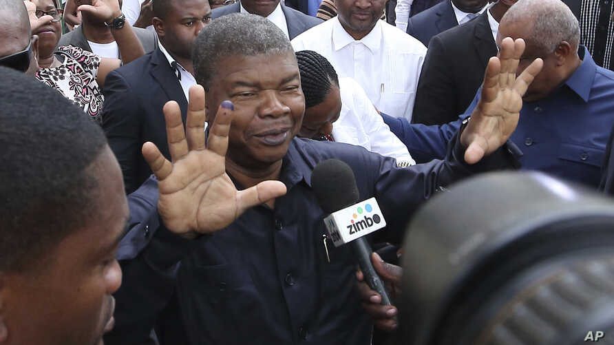 FILE -  Joao Lourenco, shows his ink-stained finger as he faces the media after casting his vote in elections in Luanda, Angola.