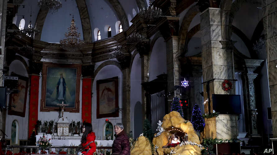 FILE - Chinese women walk past a decoration displaying a Baby Jesus doll part of a Nativity scene, at the Nantang Catholic Church in Beijing.