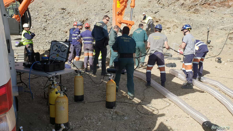 Members of a miner rescue team and rescue workers stand next to a capsule before descending into a drilled well at the area where Julen, a Spanish two-year-old boy, fell into the well 11 days ago when the family was taking a stroll through a private