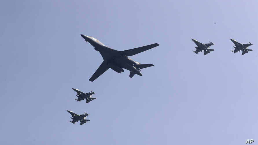 U.S. B-1 bomber, center, flies over Osan Air Base with U.S. jets in Pyeongtaek, South Korea, Tuesday, Sept. 13, 2016.