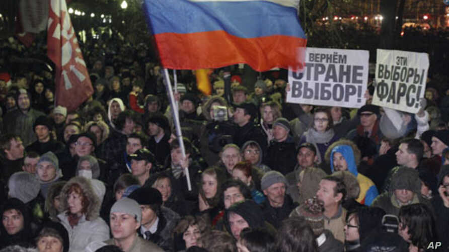 """People wave the Russian flag and hold posters reading """"This election is farce!"""" and """"Give the country choice back"""" during an opposition rally in Moscow, Russia, December 5, 2011."""