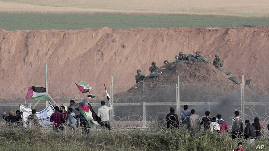 Protesters wave Palestinians flags in front of Israeli solders on Gaza's border with Israel, east of Beit Lahiya, Gaza Strip, April 4, 2018.