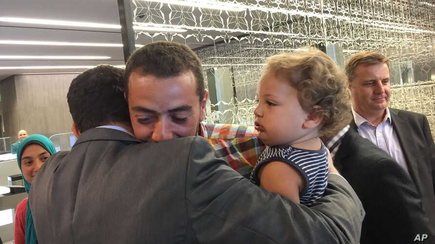 A colleague welcomes Egyptian Al-Jazeera English journalist Baher Mohammed, carrying son Haroon, upon his arrival in Doha, Qatar, Oct. 14, 2015.