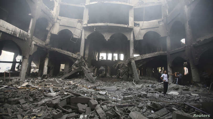 A Palestinian looks at the remains of a commercial center, which witnesses said was hit by an Israeli airstrike on Saturday, in Rafah in the southern Gaza Strip, Aug. 24, 2014.