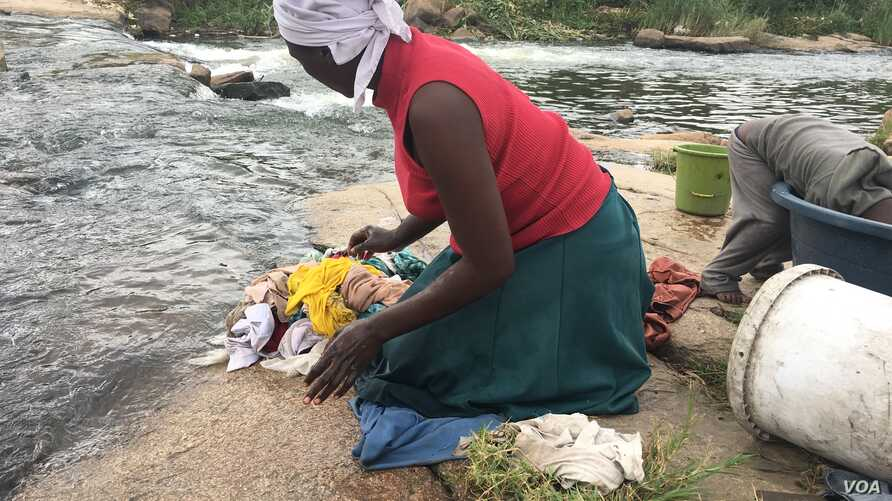 For Chipo Masvinga, right to water in Zimbabwe's constitution since 2013 is still far away, with infant daughter Esther and 4-year-old son Emmanuel, she does laundry in Mukuvisi river in Harare.  March, 2017. (C. Mavhunga/VOA)