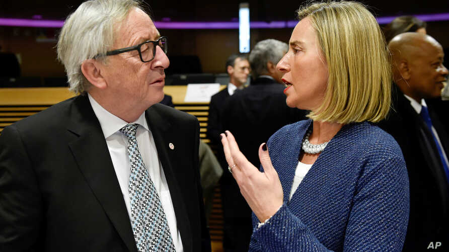 European Union foreign policy chief Federica Mogherini, right, speaks with European Commission President Jean-Claude Juncker during a round table meeting of the EU-Sahel at EU headquarters in Brussels, Feb. 23, 2018.
