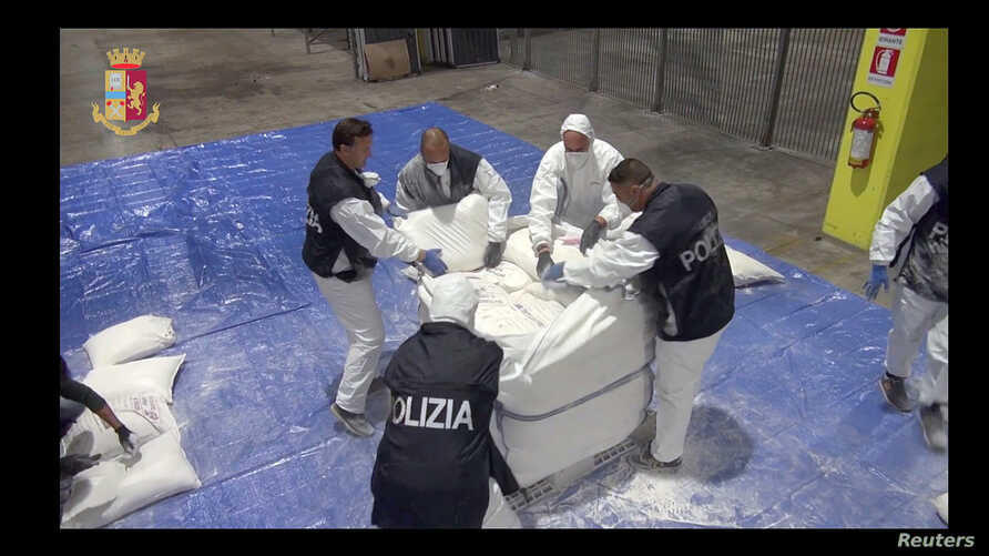 Police officers check bags found in Genoa harbour in this video grab provided by the Italian Police, Nov. 8, 2018.
