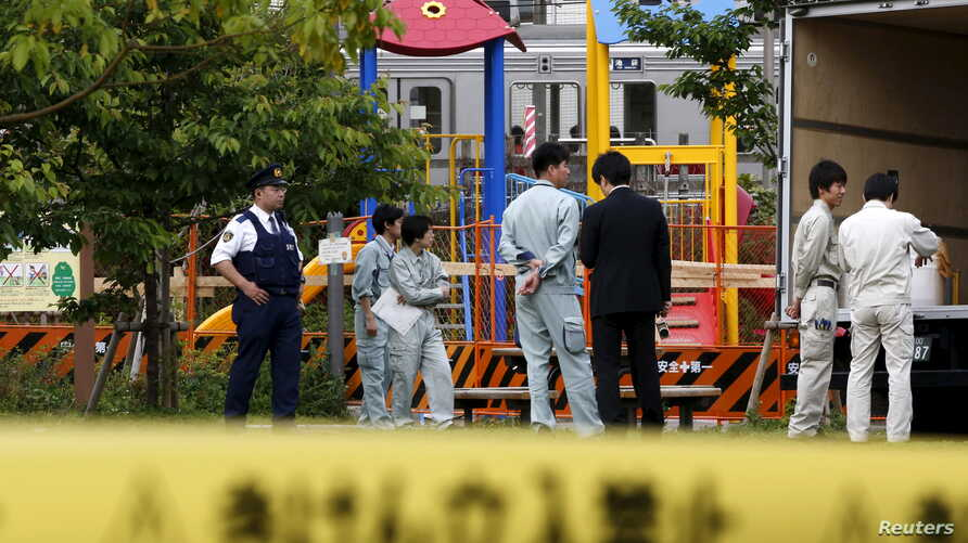 Workers of Tokyo's Toshima ward office and police officers are seen in front of the playground equipment  where high levels of radiation were detected at a park in Toshima ward, Tokyo, April 24, 2015.