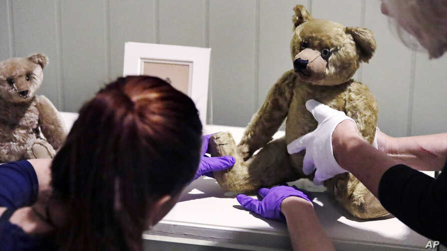 """Gallery stylists position antique Winnie the Pooh bears while preparing the """"Winnie-the-Pooh: Exploring a Classic"""" exhibit at the Museum of Fine Arts in Boston, Sept. 13, 2018."""