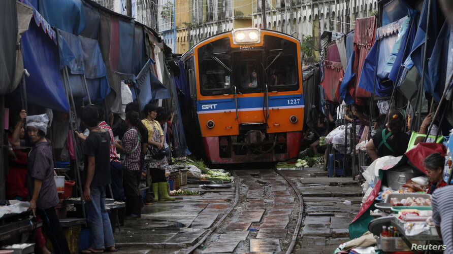Thailand's government wants to upgrade the national rail system. Venders pull back awnings and vegetables as a train arrives in Maeklong, in Samut Songkhram province, Aug. 16, 2012.