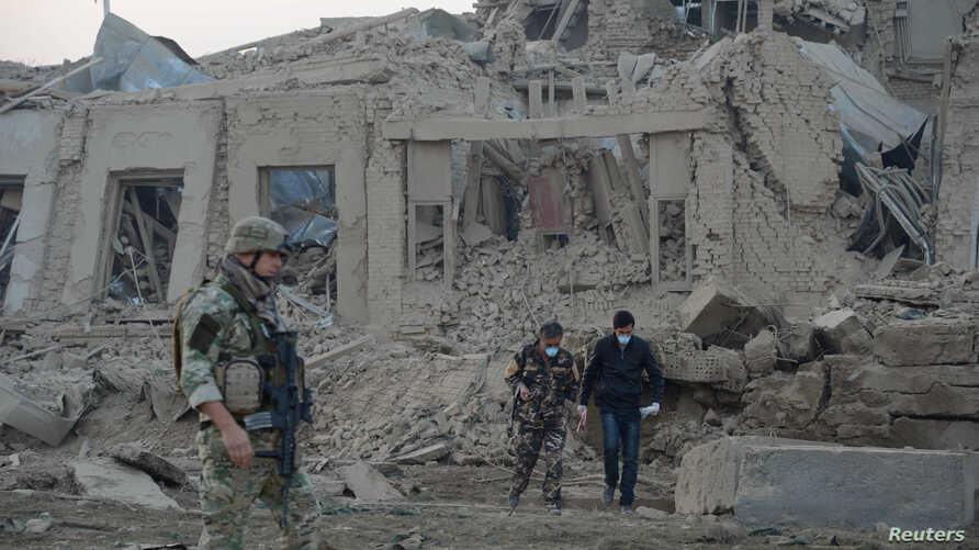 Afghan security forces and NATO troops investigate at the site of explosion near the German consulate office in Mazar-i-Sharif, Afghanistan, Nov. 11, 2016.