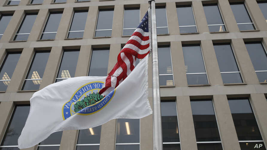 FILE - The flag of the Department of Education flies beneath the U.S. flag, at the Education Department building in Washington, April 3, 2018.