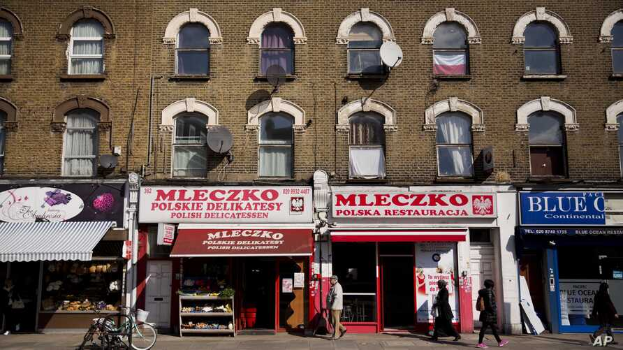 FILE - People walk past the Polish Mleczko delicatessen and restaurant in London, April 5, 2016. Following right-wing election gains, Eurosceptics in Austria and Poland are keeping a close eye on Britain's June 23rd referendum to stay or quit the Eur