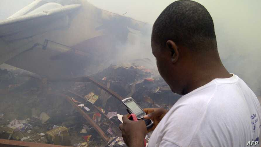 A man using his cell phone in a neighborhood just north of Murtala Muhammed International Airport, in Lagos, Nigeria, June 3, 2012.