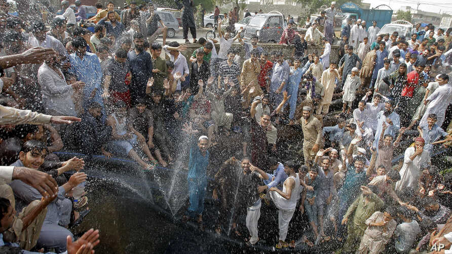 FILE - People cool off in a spray from a broken water pipe during a heat wave, in Karachi, Pakistan, May 31, 2017.