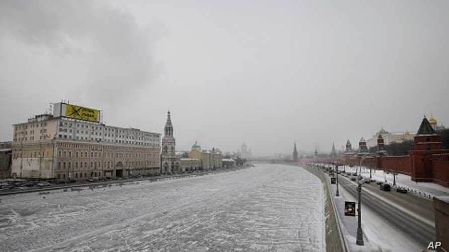 A giant anti-Prime Minister and presidential candidate Vladimir Putin billboard set up by the opposition Solidarity movement on a building, left, which faces the Kremlin, right, is seen in downtown Moscow on February 1, 2012.
