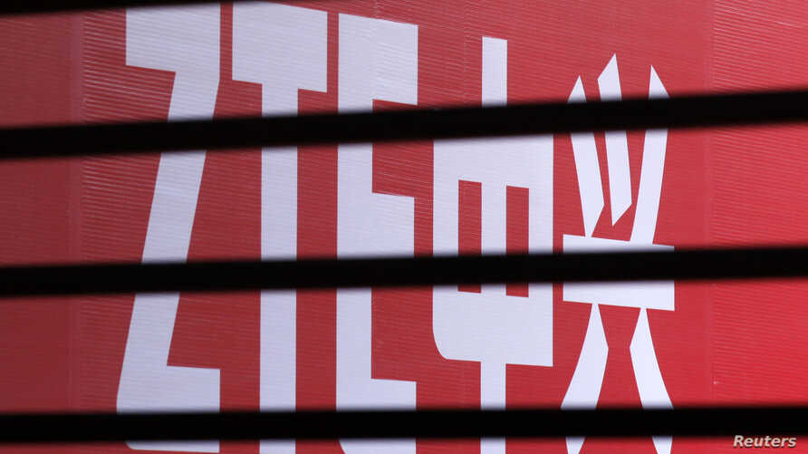The company logo of ZTE is seen through a wooden fence on a glass door in Beijing, China, April 18, 2013.