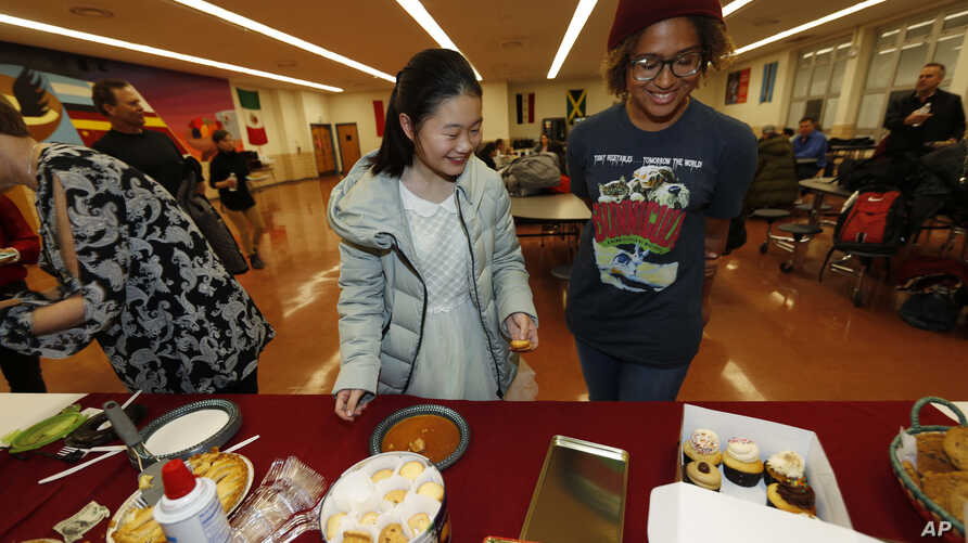 Miaofan Chen, left, works her way through the dessert choices along with Thandi Glick during a potluck meal for Chinese exchange students and their host families in Denver, Jan. 27, 2017.