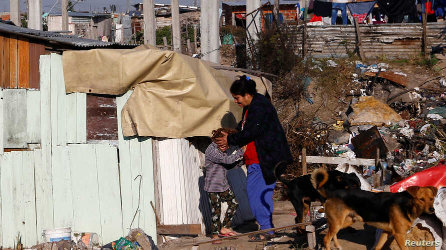 Nimia Duarte grabs her daughter Estelvina outside their shack in a slum of Villa Fiorito, on the outskirts of Buenos Aires, Argentina, June 15, 2016.