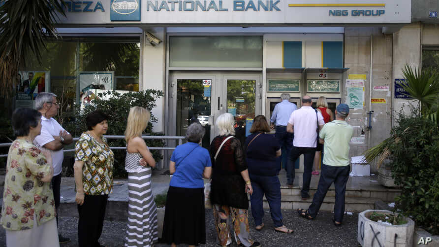People stand in a queue to use an ATM outside a closed bank, next to a sign on the plant, bottom right, reading ''NO'' in Athens, June 30, 2015.