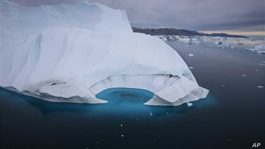 FILE - In this July 19, 2007 file photo, an iceberg is seen melting off the coast of Ammasalik, Greenland.  A new assessment of climate change in the Arctic shows the ice in the region is melting faster than previously thought and sharply raises proj