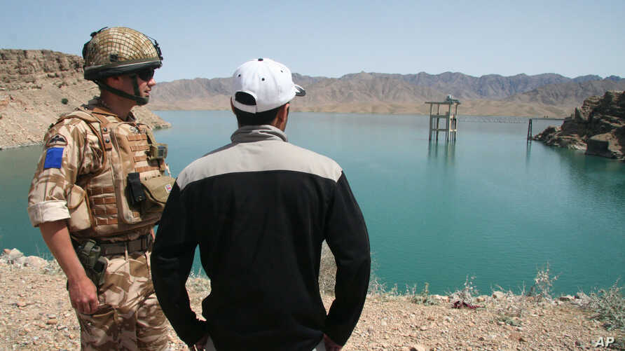 A British soldier stands with an Afghan interpreter with part of the Kajaki power dam in the background in Kajaki, Helmand province, south of Kabul, Afghanistan, April 16, 2008.