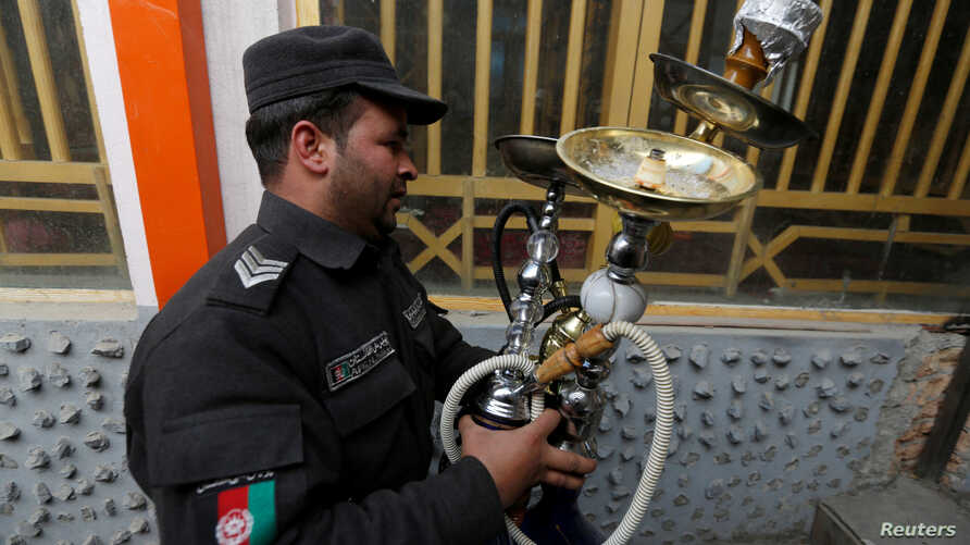 A policeman confiscates shisha water pipes from a shisha cafe during a raid in Kabul, Afghanistan, Nov. 27, 2016.