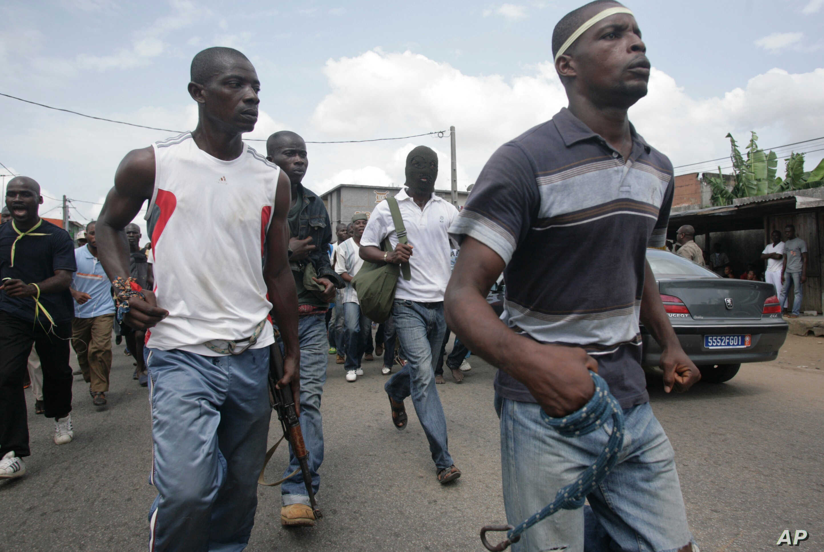 FILE - Youths loyal to Laurent Gbagbo carry homemade weapons and a gun as they heed a call from youth leader Charles Ble Goude, not pictured, to form 'self-defense' units to protect against rebels, in the Youpougon district of Abidjan, Ivory Coast, F